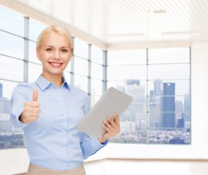 businesswomen le pouce tendu vers le haut, souriant et tenant une tablette